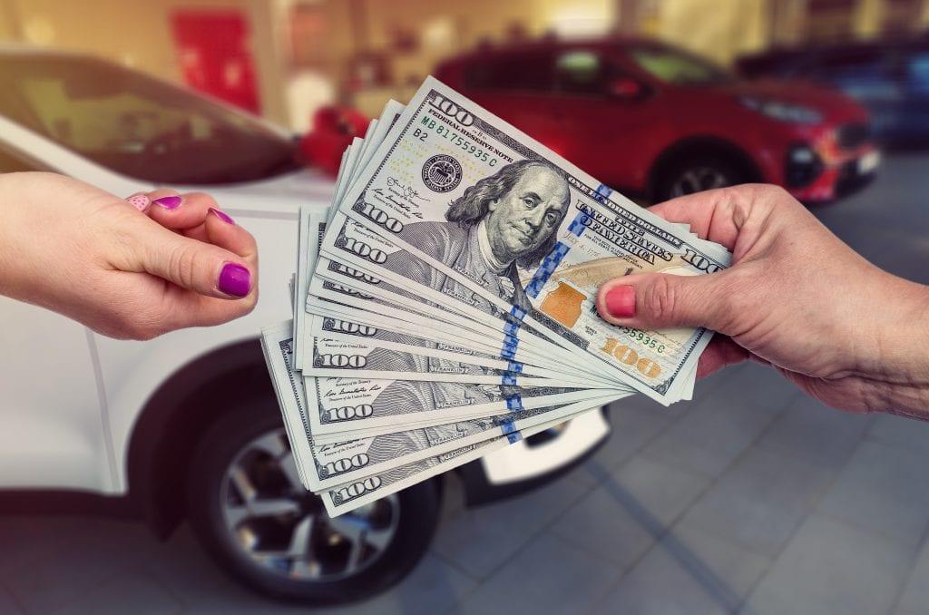 Seller receiving cash payment for their junk car.